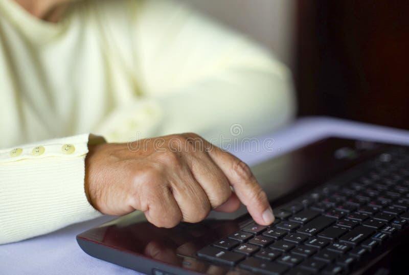 Ältere Hand der alten Frau der Nahaufnahme auf surfendem Internet der Laptoptastatur zu Hause mit freiem und Kopienraum stockbild