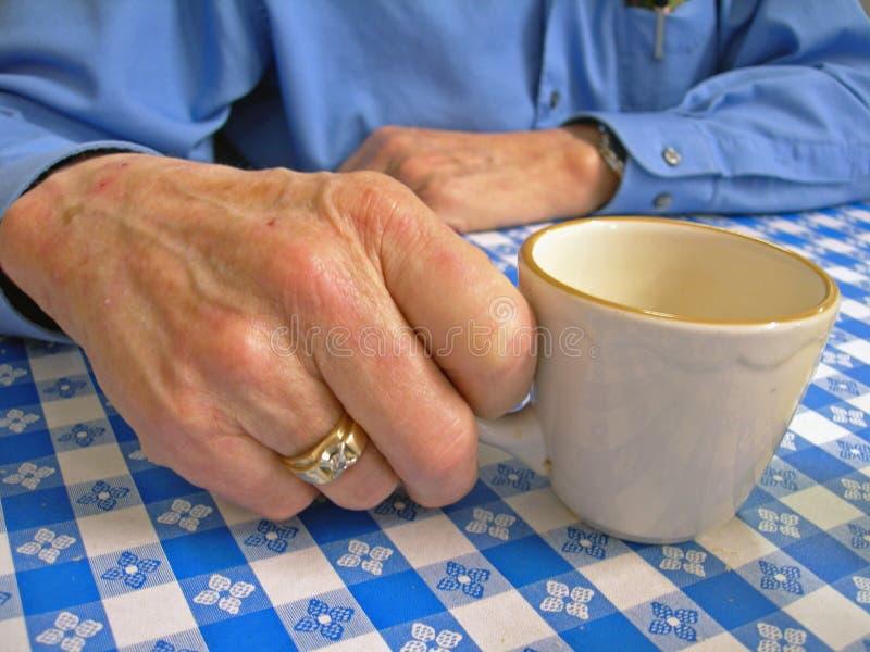 Ältere Hand mit Kaffeetasse lizenzfreies stockfoto