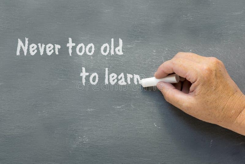 Ältere Hand schreibt auf eine Tafel: Nie zu alt lernen stockbild