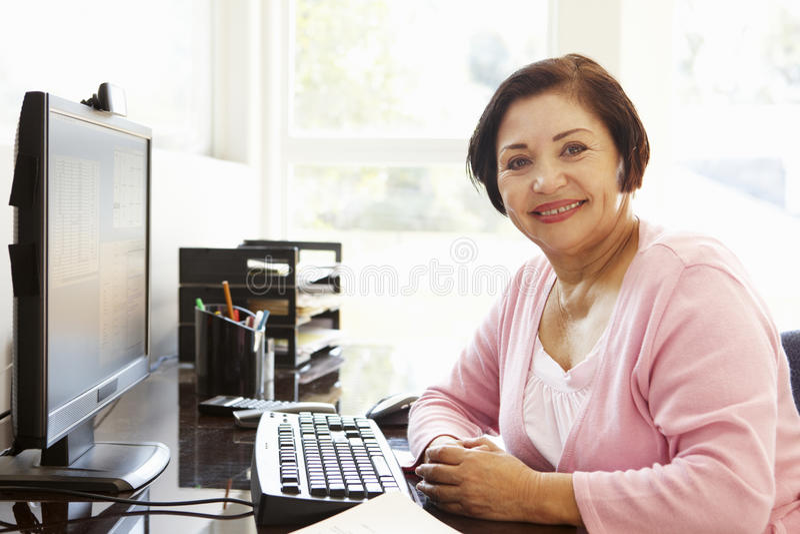 Ältere hispanische Frau, die zu Hause an Computer arbeitet stockbilder