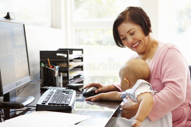 Ältere hispanische Frau mit Computer und Baby lizenzfreie stockfotos