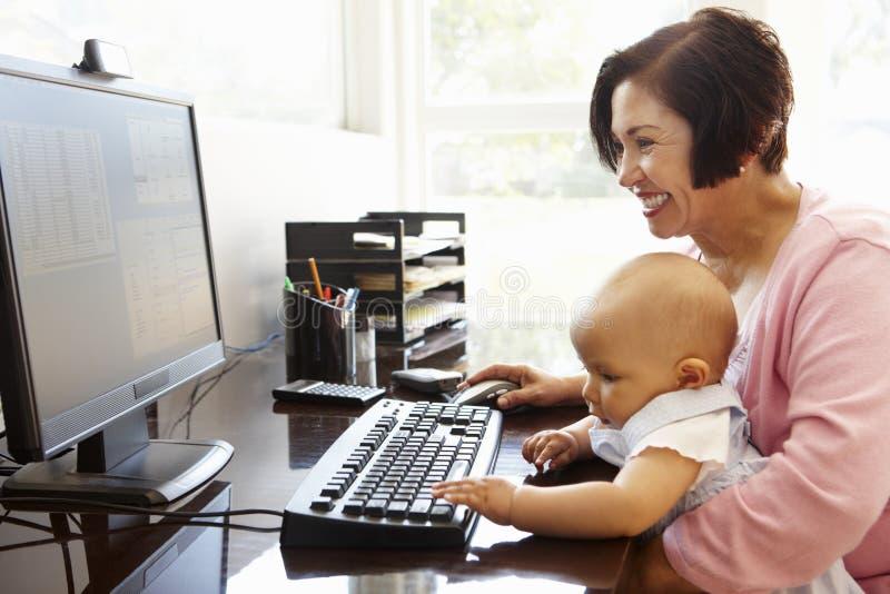 Ältere hispanische Frau mit Computer und Baby stockfotos