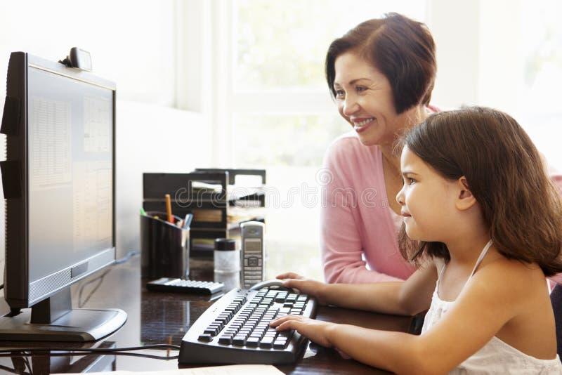 Ältere hispanische Frau mit Computer und Enkelkind lizenzfreie stockfotos