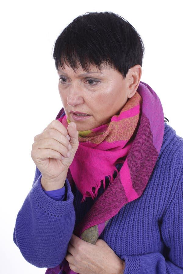Ältere hustende Frau mit Schal und Pullover lizenzfreie stockbilder