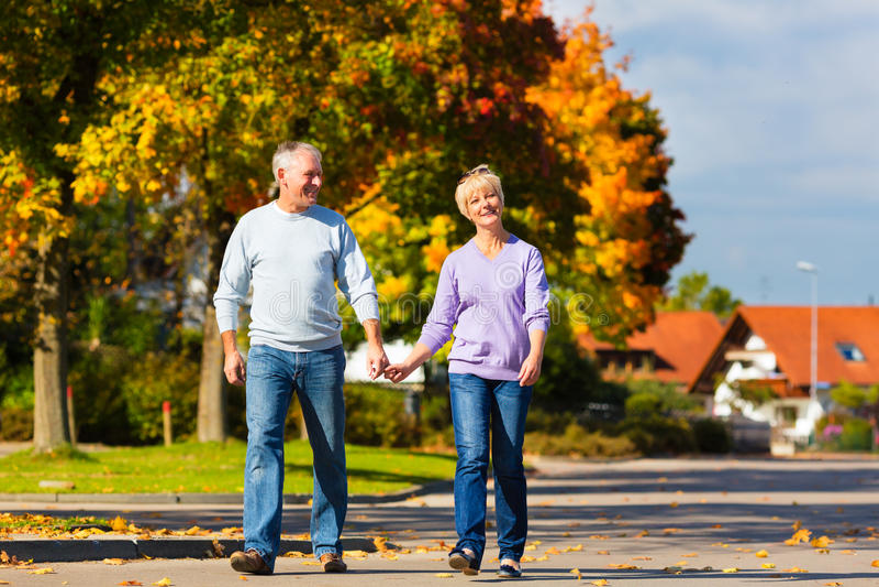 Ältere im Herbst oder im Fall Hand in Hand gehend stockfotos
