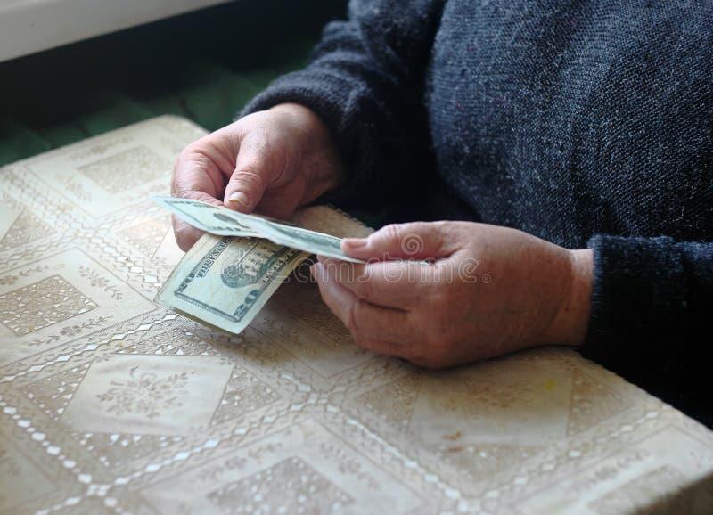 Ältere kaukasische Frau, die Geld auf Tabelle zählt lizenzfreie stockfotografie