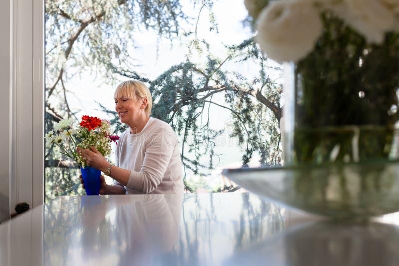 Ältere kaukasische Frau mit Blumen zu Hause stockfotos