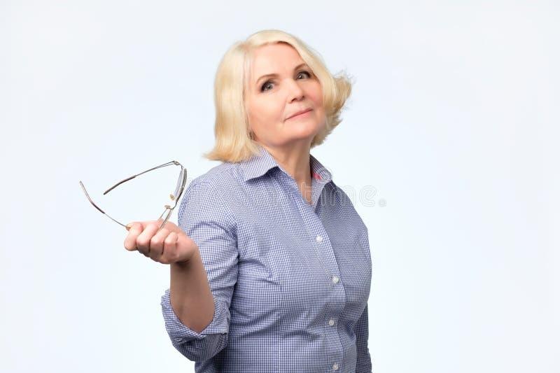 Ältere kaukasische Frau mit dem blonden Haar im weißen und gelben Strickjackenlächeln stockfotografie