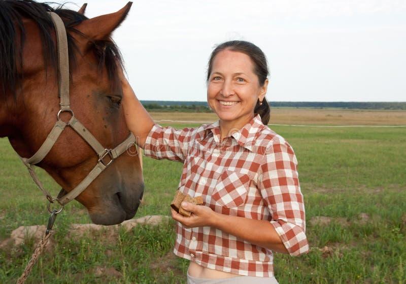Ältere kaukasische Frau mit Pferd lizenzfreies stockfoto