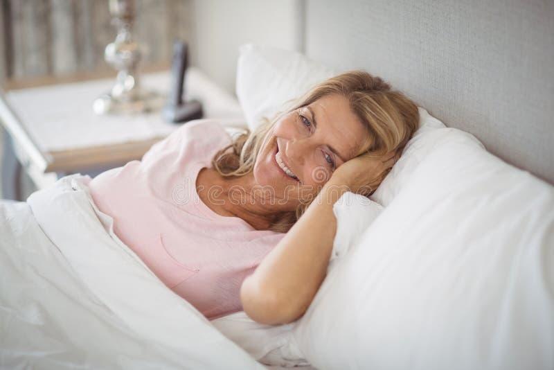 Ältere lächelnde Frau beim Stillstehen auf Bett lizenzfreie stockfotos