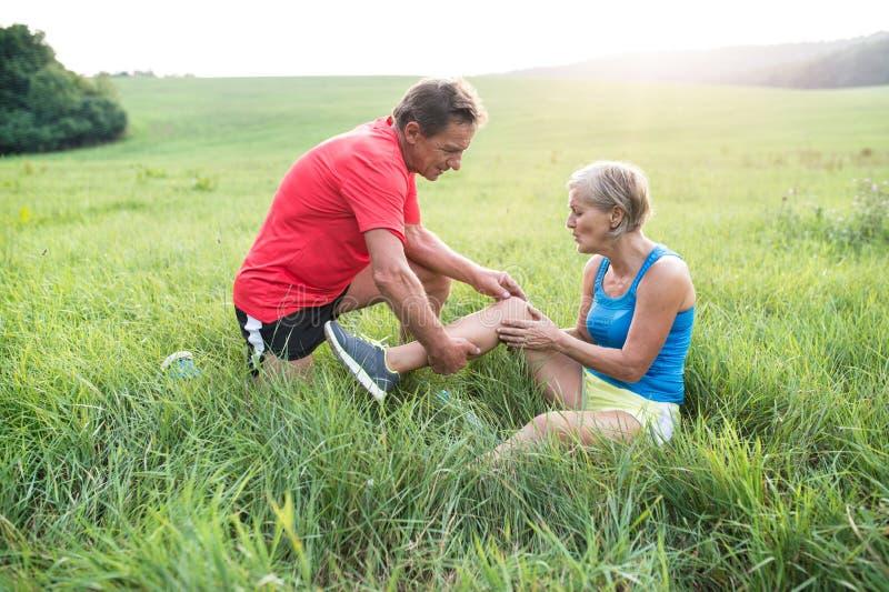 Ältere Läufer auf dem grünen Gebiet Frau mit verletztem Knie stockbilder