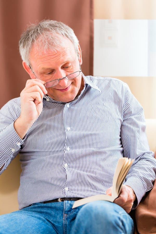 Ältere Lesung mit Presbyopiebeipackzettel stockfotografie