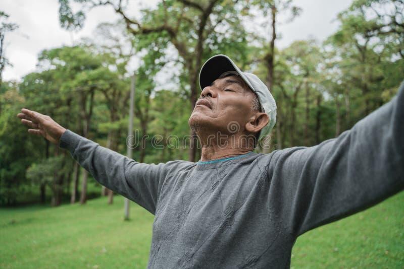 Ältere Leute atmen ausdehnen heraus und anheben Arm tief ein stockbild