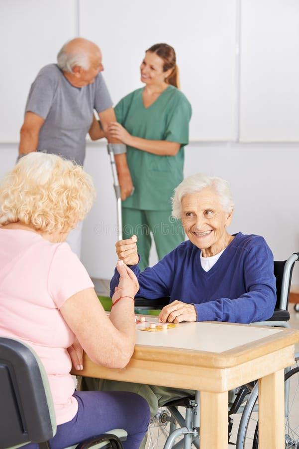 Ältere Leute, die Bingo im Pflegeheim spielen lizenzfreie stockfotografie
