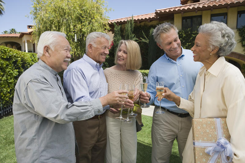 Ältere Leute, die im Garten rösten lizenzfreie stockfotos