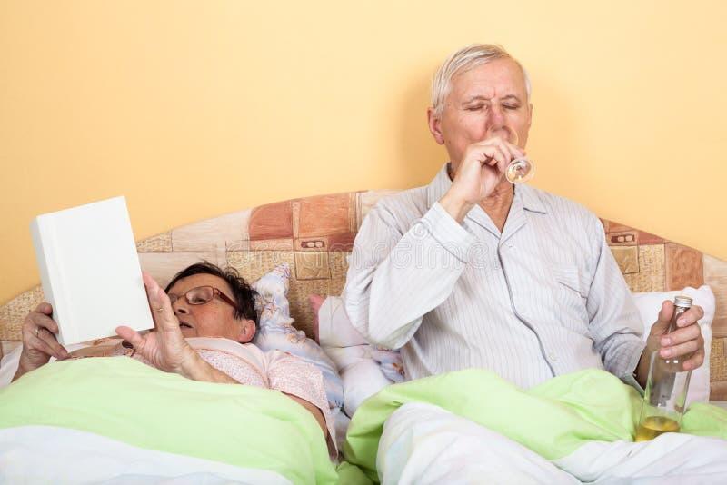 Senioren entspannen sich mit Alkohol im Bett stockfoto