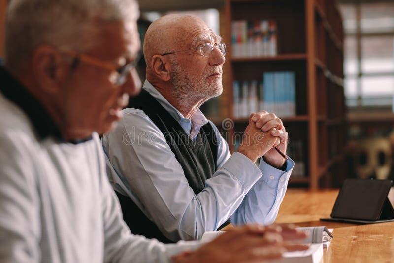 Ältere Männer, die in einem Klassenzimmerlernen sitzen lizenzfreies stockbild