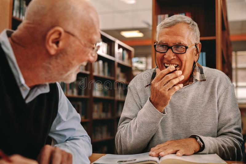 Ältere Männer, die in einer Bibliothek und in einem Studieren sitzen lizenzfreie stockbilder