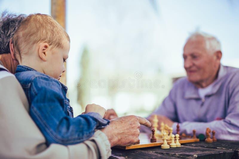 Ältere Männer, die Spaß haben und Schach am Park spielen stockbild