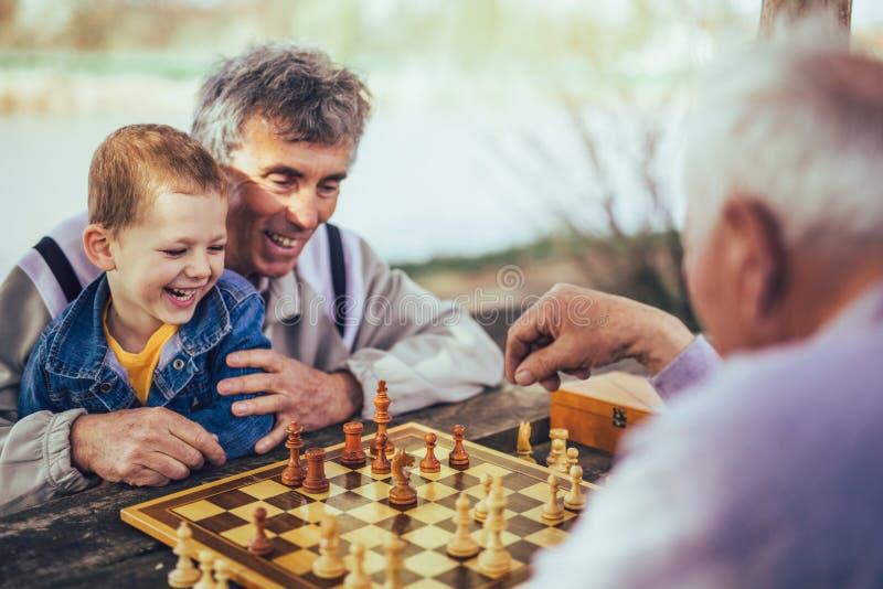 Ältere Männer, die Spaß haben und Schach am Park spielen stockfotos