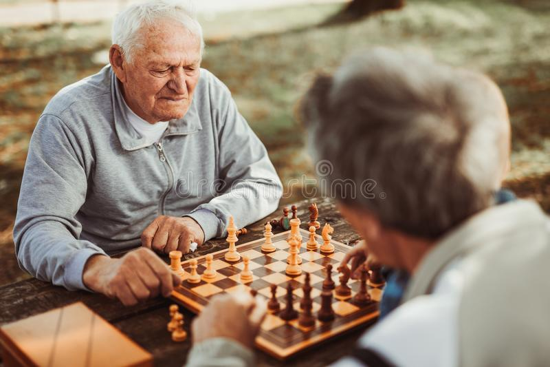 Ältere Männer, die Spaß haben und Schach spielen stockfotografie