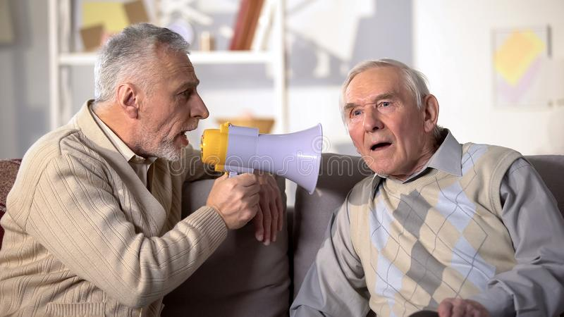 Ältere Männer sprechen in Megaphone zu taub alten Freund, Gesundheitsprobleme, Nahaufräumung stockfotografie