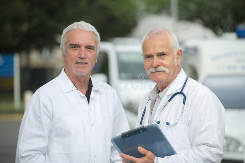 Ältere männliche Doktoren, die weißen Laborkittel außerhalb des Krankenhauses tragen lizenzfreies stockfoto