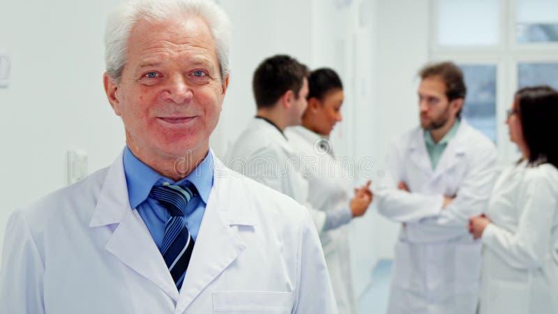 Ältere männliche Doktorhaltungen am Krankenhaus lizenzfreies stockbild