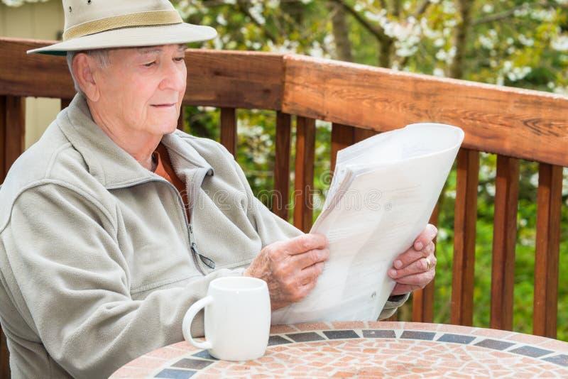 Ältere Mann-Lesezeitung und trinkender Kaffee lizenzfreies stockbild