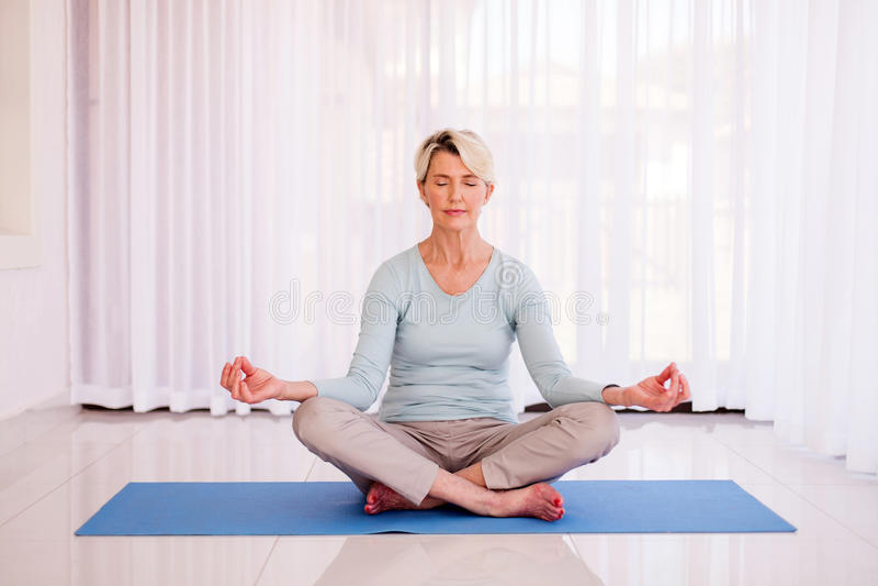 Ältere meditierende Frau stockfotografie