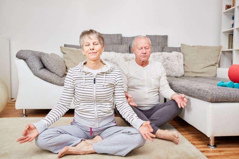 Ältere meditierende Paare stockbild