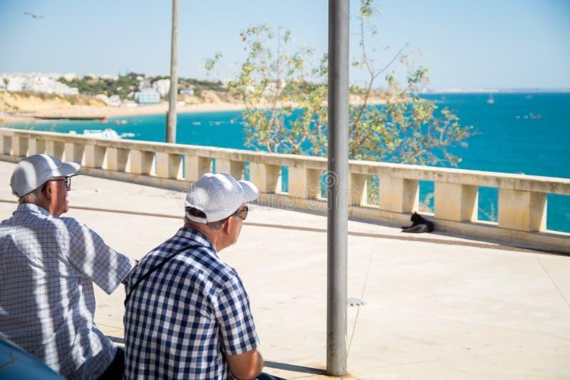 Ältere Menschen, die am Standpunkt in Albufeira sitzen und das Algarvian-Meer aufpassen lizenzfreies stockfoto
