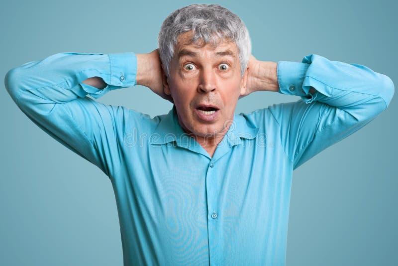 Ältere Mitte alterte grauen behaarten Mann hält Hände hinter Kopf, anstarrt im Unglauben, trägt formales Hemd, Haltungen gegen bl lizenzfreies stockfoto