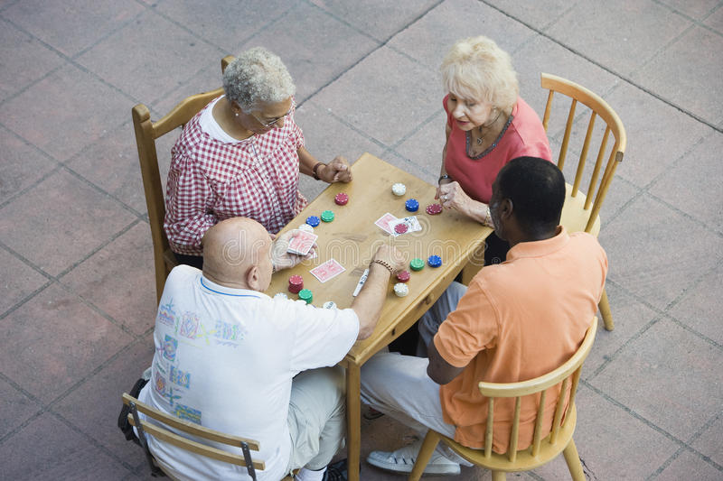 Ältere multiethnische Freund-Spielkarten zusammen lizenzfreies stockbild