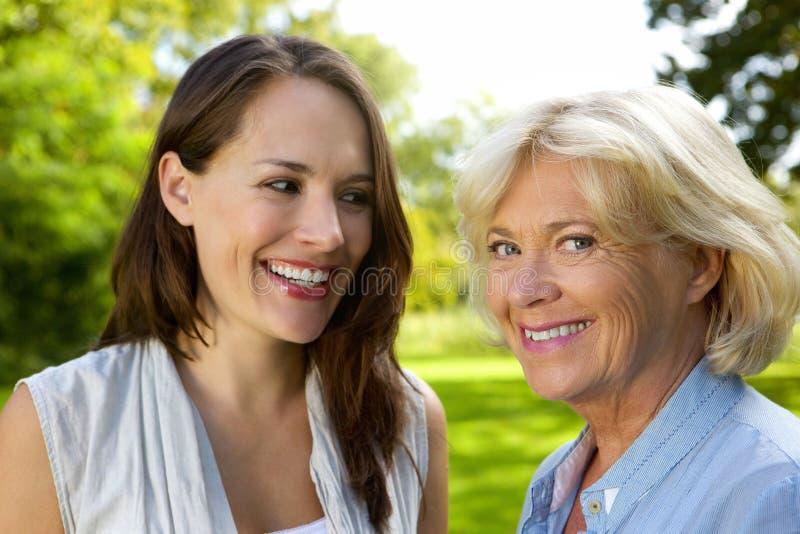 Ältere Mutter, die mit älterer Tochter lächelt stockbild