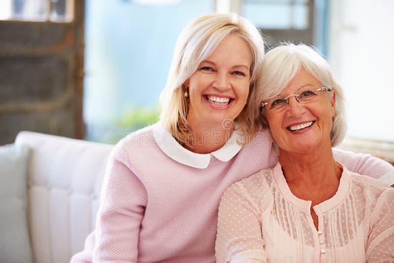 Ältere Mutter mit der erwachsenen Tochter, die auf Sofa sich entspannt stockbilder