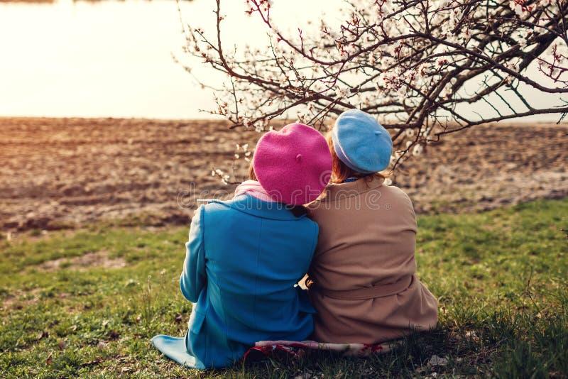 Ältere Mutter und ihre erwachsene Tochter, die durch Fluss sitzt und umarmt Mutter ` s Tageskonzept Familienwerte lizenzfreies stockfoto
