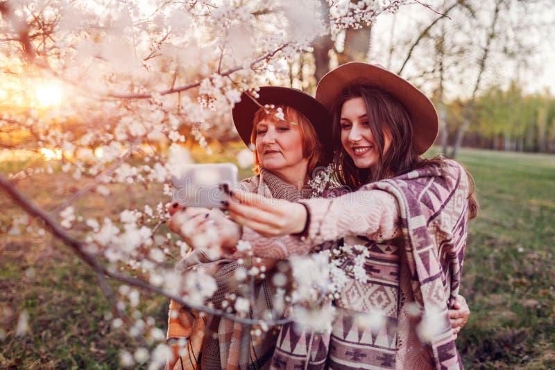 Ältere Mutter und ihre erwachsene Tochter, die selfie in blühendem Garten umarmt und nimmt Mutter ` s Tageskonzept Familienwerte stockfotos