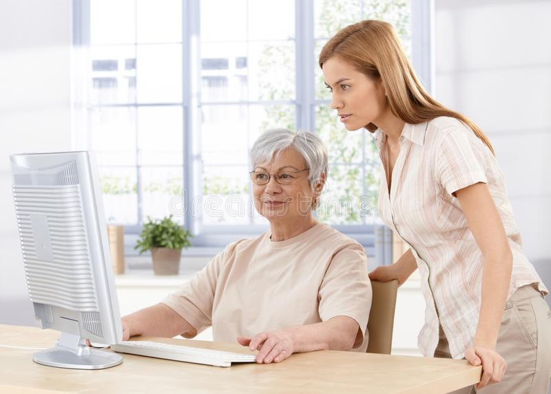 Ältere Mutter und Tochter, die Computer verwendet stockfotografie