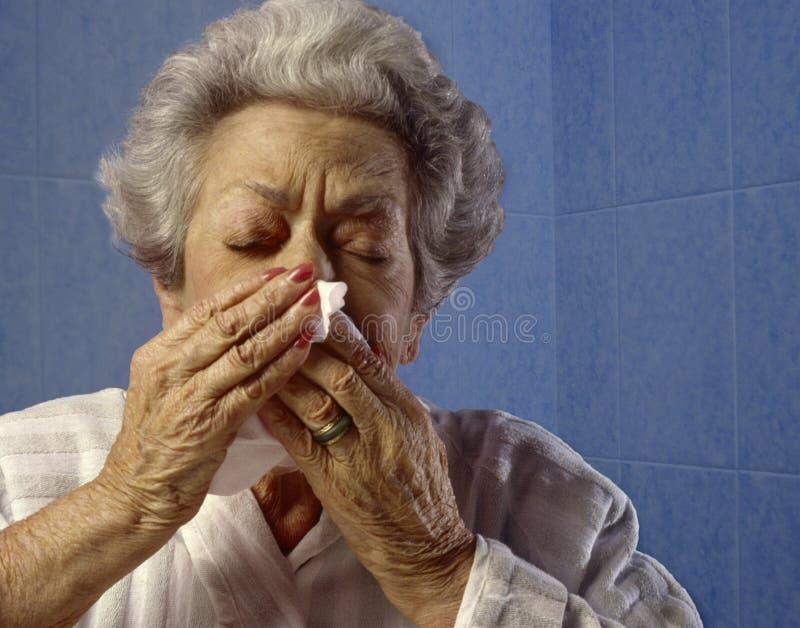 Ältere niesende Frau stockfoto