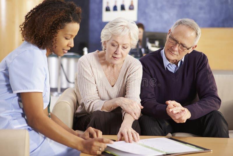 Ältere Paar-Sitzung mit Krankenschwester In Hospital lizenzfreie stockbilder