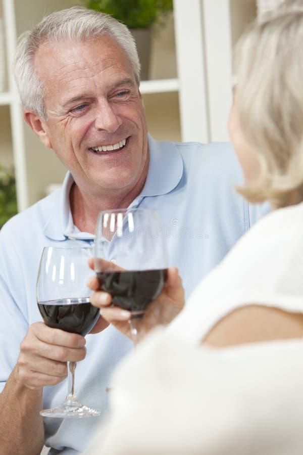 Ältere Paar-trinkender Wein zu Hause lizenzfreie stockfotos