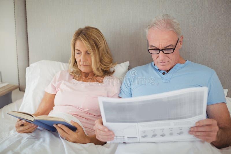 Ältere Paare auf Bettlesezeitung und -buch lizenzfreie stockbilder