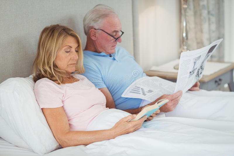 Ältere Paare auf Bettlesezeitung und -buch lizenzfreie stockfotos