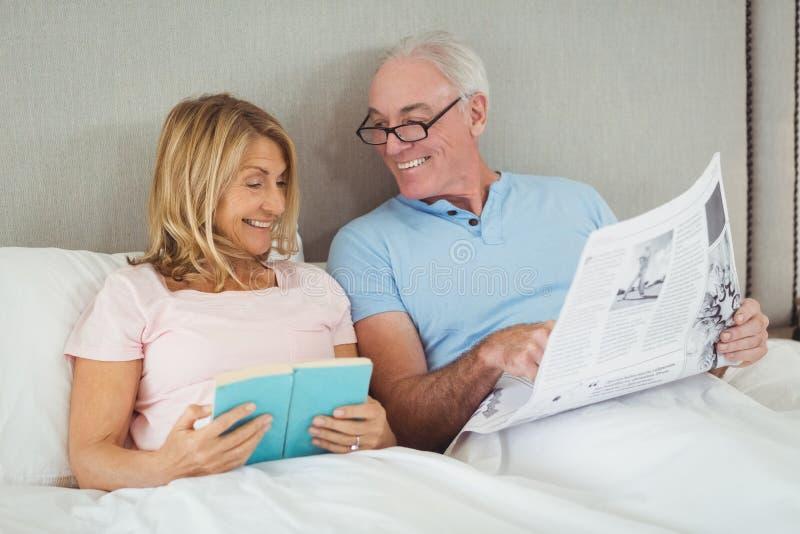 Ältere Paare auf Bettlesezeitung und -buch stockbild