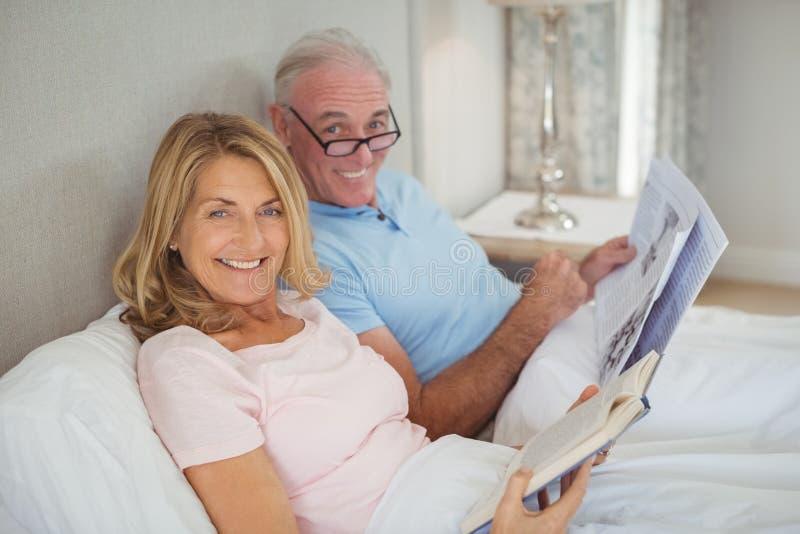 Ältere Paare auf Bettlesezeitung und -buch lizenzfreie stockfotografie