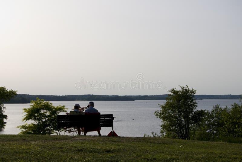 Ältere Paare auf einer Parkbank auf einer Sommerglättung. lizenzfreie stockbilder