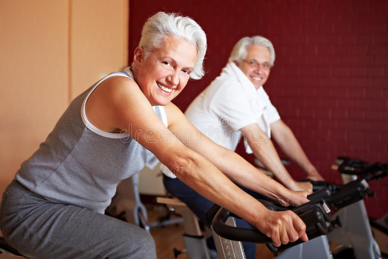 Ältere Paare auf spinnenden Fahrrädern lizenzfreie stockfotografie