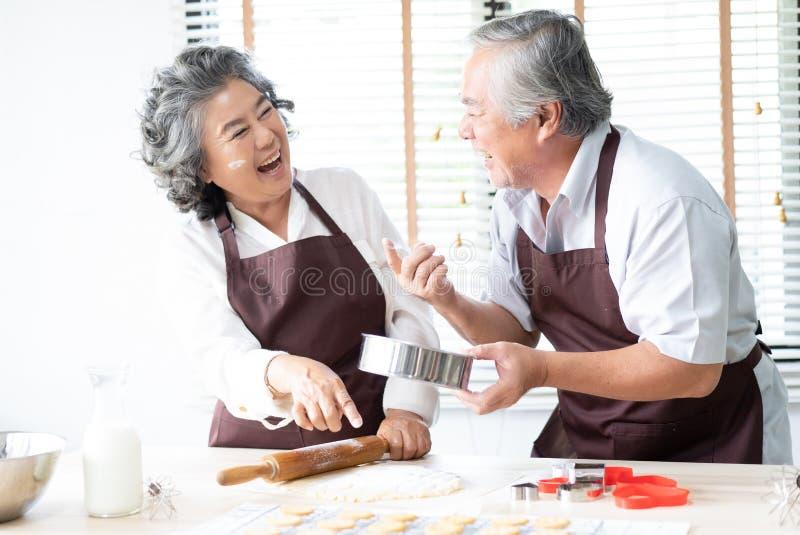 Ältere Paare der glücklichen Familie besprühen den Teig mit Mehl und lachen beim Küche der Plätzchen zu Hause backen Backen und lizenzfreies stockfoto