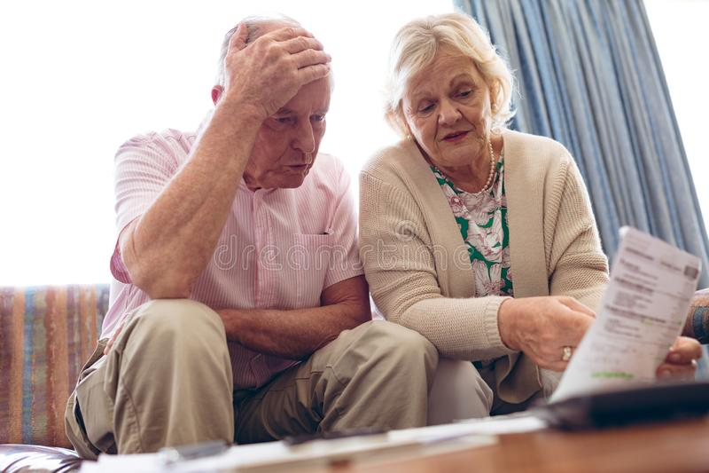 Ältere Paare, die über Arztrechnung beim Sitzen auf Sofa am Ruhesitz sich besprechen lizenzfreie stockfotografie